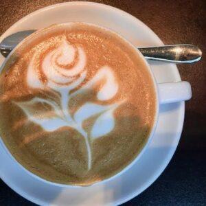 Eine Rose mit Latte Art gezeichnet, also der Kunst mit perfekten Milchschaum ein Bild in den Kaffee zu malen. Horst hat dies bereits auf Meisterschaften getan. Auf dem Bild sieht man die weiße Tasse von oben, auf einer Untertasse mit einem Cappuccino Löffel an der oberen Seite