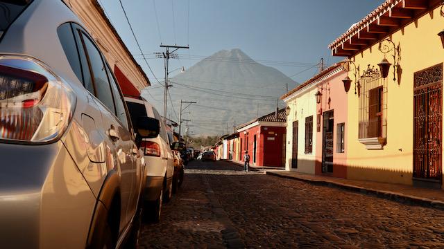 Eine Straße in Antigua, Guatemala, mit einem Vulkan im Hintergrund.