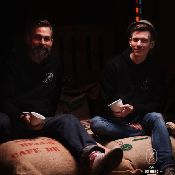 Sebastian und Johannes auf Kaffeesäcken in ihrer Rösterei.