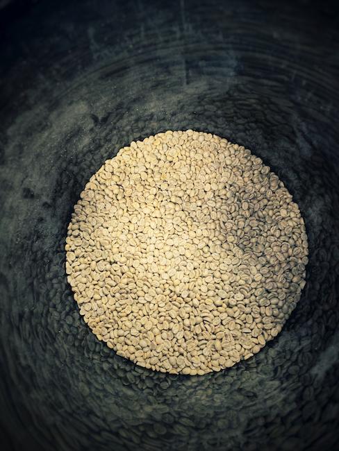 Grüne Kaffeebohnen in einem Eimer. Das hier noch grüne Gold wird emotional beworben. Nicht immer mit viel echter Information.