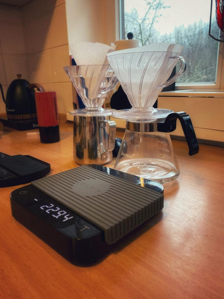 Ausrüstung zum Kaffee kochen. Zwei Hario V60 Filter mit Glaskanne, eine Acaia Kaffeewaage und im Hintergrund eine rote Commandante Hand Kaffeemühle