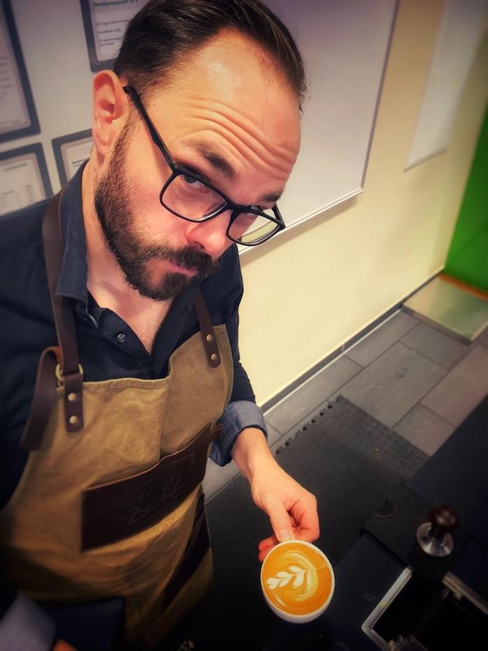 Ein Barista bei seiner Arbeit. Hier halte ich einen liebevoll produzierten Cappuccino in der Hand. Die Herausforderung sind vielfältig.