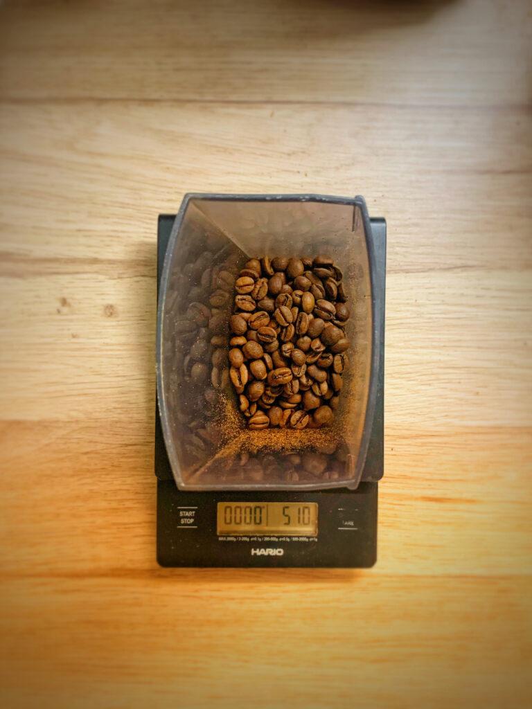 Hario Waage zum Kaffee kochen. Auf ihr steht ein Bohnenbehälter mit zu mahlendem Kaffee.