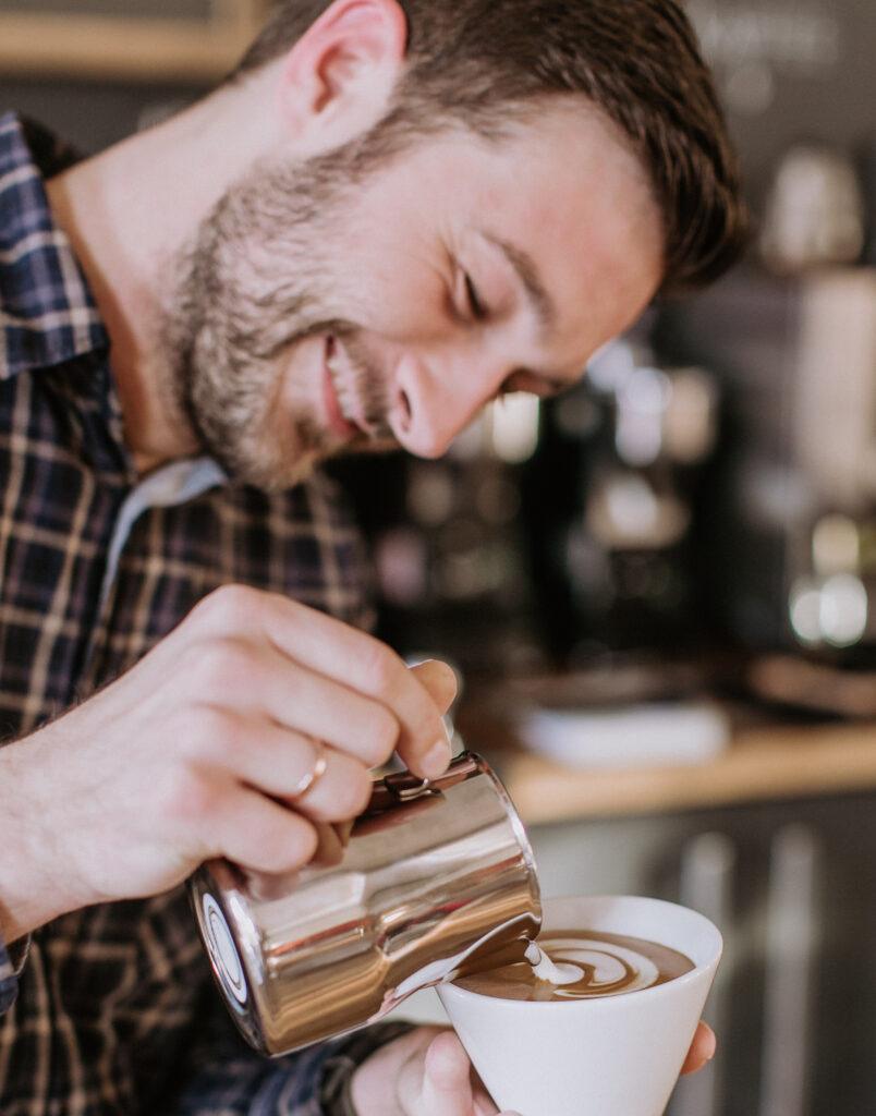 Barista Christian Ullrich beim Latte Art gießen.