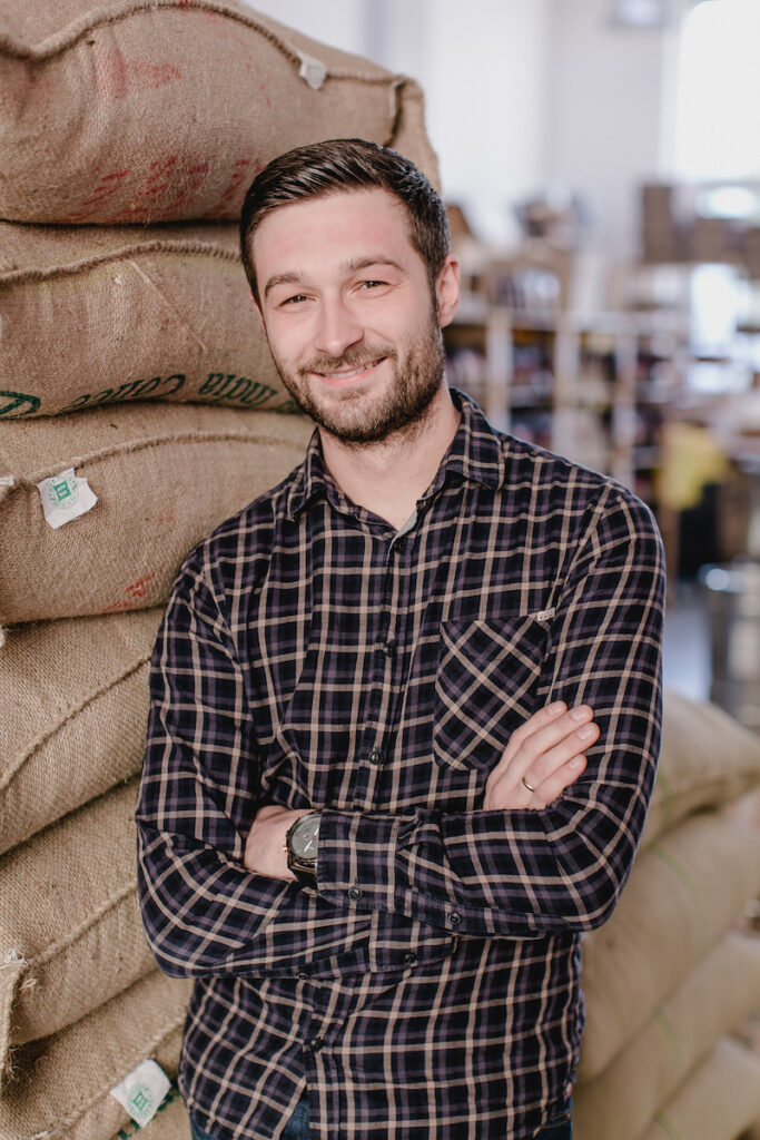 Barista Christian Ullrich steht vor Kaffeesäcken mit Grünkaffee