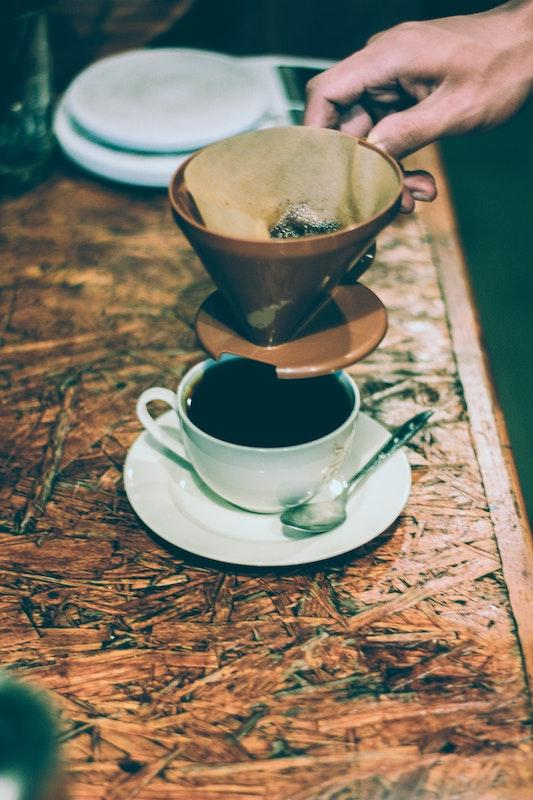 Handgefilterter Kaffee auf einem Tisch. Der Kaffeefilter ist in der Kaffee Geschichte ein Meilenstein.
