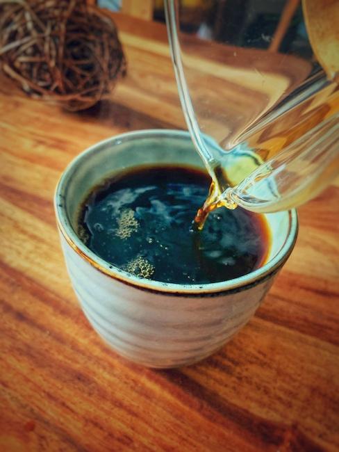 Eine Tasse Kaffee wird auf einem Holztisch eingeschränkt. Warme Materialien sind ein Weg für angenehmes Ambiente zu sorgen.