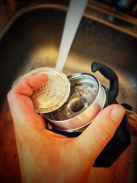 Ein auseinandergeschraubter Mokka Pot bei der Reinigung unter fließendem Wasser. Das ist ein wichtiger Teil um immer leckeren Kaffee machen zu können.