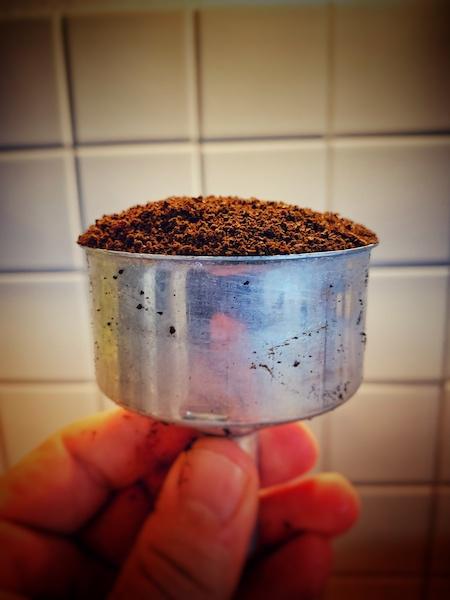Ein mit Kaffeemehl gefülltes Sieb von einem Mokka Pot. In der Mitte sollte noch eine kleine welle sein, bevor man es dann flach klopft.