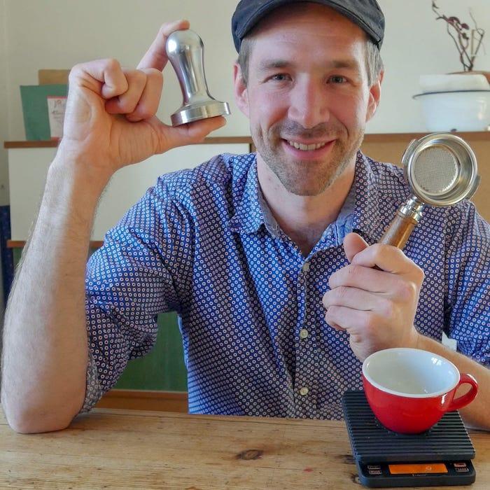 Andi mit seinem Werkzeug für seine Pädagogik im Kaffee in der Hand.