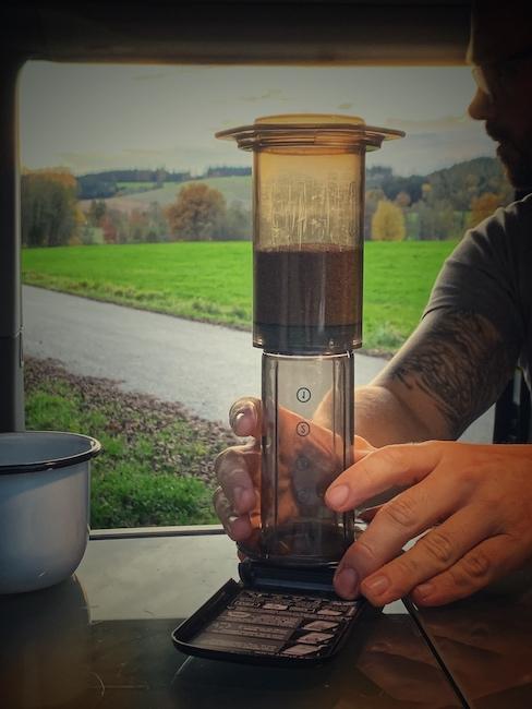 Kaffee machen beim Camping oder im Van, geht sehr gut mit einer Aero Press. So ein Gerät siehst du in diesem Bild. Im Hintergrund ist eine Straße und eine Grüne Wiese.