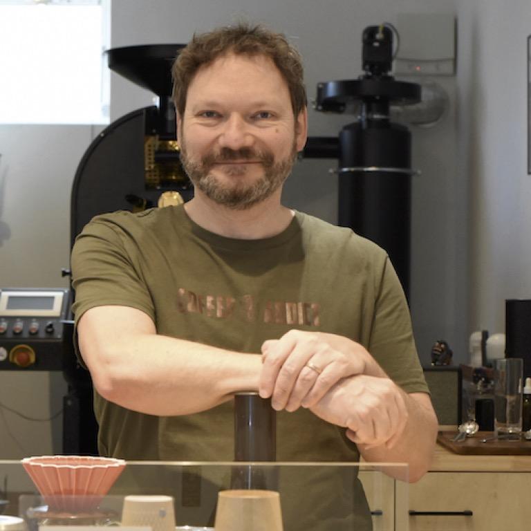 Günter steht mit grünem Hemd stolz in seiner Kaffeerösterei in Japan. Er lächelt in die Kamera. Im Hintergrund sieht man seine selbst importierte Röstmaschine und im Vordergrund den nagelneuen Origami Dripper