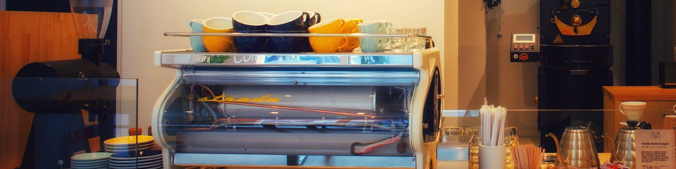 Hier siehst du Günters Kaffeerösterei Tora Coffee Roasters in Japan aus der Gastperspektive. Eine Holztheke mit einer La Marzocco Siebträgermaschine darauf, verschiedene Zubereitungsmethoden, Milchkännchen usw. auf der Bar. Im Hintergrund hängt an einer Wand auf Holz geschrieben das Kaffeemenü und hinten rechts in der Ecke steht die Kaffeeröstmaschine. Ein Probat 5kg Röster, Probatone 5.