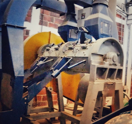 Eine große Maschine mit einer Walze in einem Gehäuse. Sie entfernt die Pergamenthaut vom Rohkaffee, bevor er für den Kaffeeexport sortiert wird.