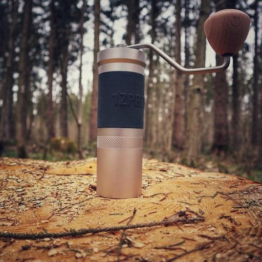 Die manuelle Kaffeemühle 1Zpresso JX Pro steht auf einem Holzstamm im Wald.