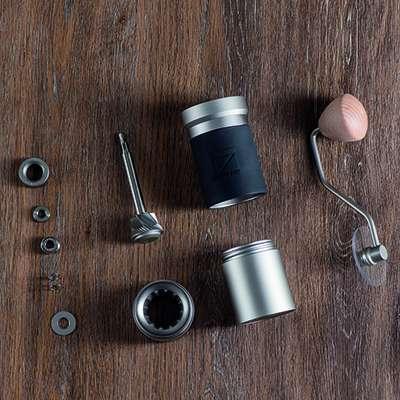 Die 1Zpresso JX Pro in ihre Einzelteile Zerlegt auf einem dunklen Holztisch. Man kann an dieser Mühle alles auseinander nehmen, inkl. dem Mahlwerk und den Kugellagern.