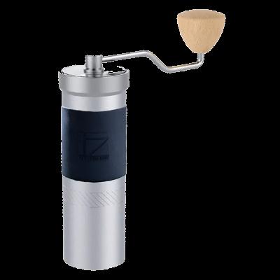 Die silberne 1Zpresso JX Pro Handkaffeemühle mit schwarzem Silikonband und hellem Holzgriff an der Kurbel steht vor weißem Hintergrund