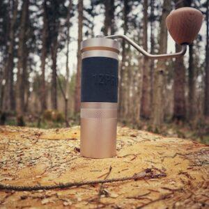 Die solide 1Zpresso JX Pro Kaffeemühle steht dekorativ auf einem Holzstamm im Wald. Sie ist silbern und aus dickem Metall gefertigt. An ihrem Körper ist ein schwarzer Silikonstreifen für besseren Halt. Der Drehknauf am Hebel ist aus hellem Holz gefertigt.