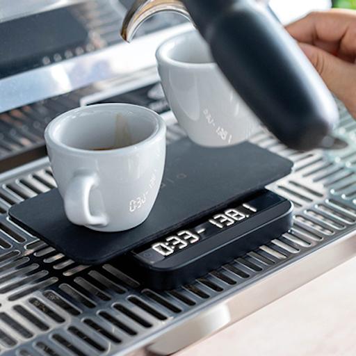 Die Acaia Lunar im Einsatz bei der Espressozubereitung. Auf ihrer Hitzefesten Auflage stehen zwei weiße Espressotassen. Die Waage ist eingeschaltet und zeigt werte an. Die Kaffeewaage selbst steht auf dem Abtropfgitter einer Siebträgermaschine.