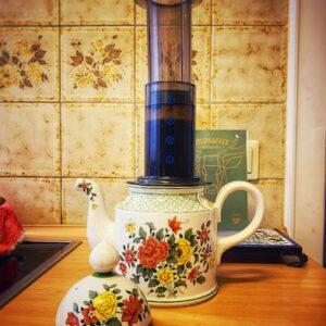 AeroPress Coffee and Espresso Maker, das Gerät steht ganz unüblich auf einer mit Blumen bedruckten alten und ganz klassischen Kaffeekanne, in einer alten Küche. Spannende Kombination aus Moderne und Tradition.