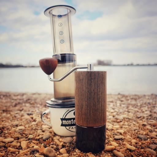 AeroPress Coffee and Espressomaker im Outdoor Kaffee Einsatz. Das Gerät steht auf einer Emaille Tasse, im Vordergrund steht eine Commandante Kaffee Mühle, die nicht zum Lieferumfang gehört. Alle drei Teile stehen auf einem Kiesuntergrund an einem See.