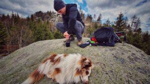Niklas von Backpack of Freedom bei seinem Hobby, beim Wandern Kaffee kochen, echten Outdoor Kaffee eben. Er ist in der Hocke auf einem großen Felsen. Vor ihm auf dem Boden steht eine Aero Press Go Coffee Maker, in dem er gerade einen Kaffee brüht. Im Vordergrund liegt sein Hund und rechts von ihm sein schwarzer Rucksack.