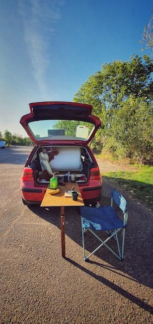 Der Micro Camper von Backpack of Freedom. Ihn hat Niklas selbst ausgebaut und ist viel mit ihm unterwegs, auch um draußen Kaffee zu machen. Es handelt sich um einen Golf 4 in rot. Aus seinem Kofferraum kommt ein selbstgebauter Holztisch, der mit einem Standbein auf dem Parkplatz steht. Auf dem Tisch liegt Ausrüstung für eine Brotzeit und neben ihm steht ein Campingstuhl.