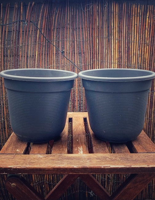 Vor einer mit Weidenzaun bedeckten Wand stehen zwei graue Blumenkübel auf einem mittelbraunen Holzschemel. Wir betrachten die Szene seitlich und können daher nicht sehen was in den Kübeln ist. Aus dem Kontext wissen wir aber, dass es Teil der Verniedlichung zur Wirkungsweise des Kaffee Mahlgrads ist. Also wie beeinflusst der Mahlgrad den Kaffee?