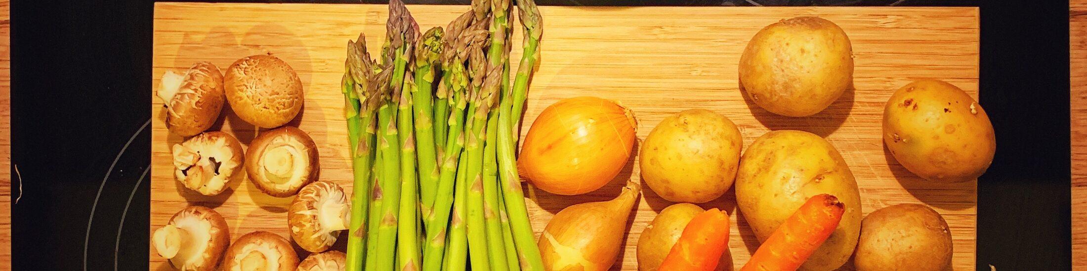 Gemüse auf einem Holzbrett. Es liegt bereit zum Kochen, muss aber noch geschnitten werden. Über dem Brett stehen Schüsseln. Auch beim Kochen ist Gleichmäßigkeit wichtig. Hier sieht man Champignons, Spargel, Kartoffeln und Möhren.