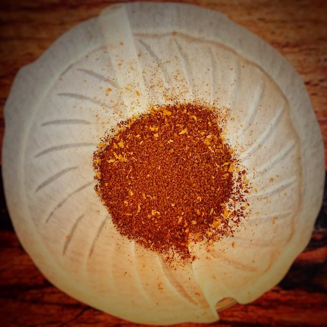 Ein Kaffeefilter, genauer ein Hario V60, aus der Vogelperspektive aufgenommen. In ihm sieht man gleichmäßig verteilt und gemahlen das Kaffeemehl. Die Gleichmäßigkeit ist bei der Kaffeezubereitung sehr wichtig.