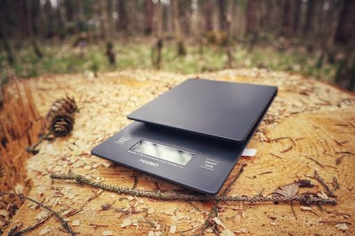 Die Hario Drip Scale Kaffee Waage liegt Brandneu auf einem Holzstamm im Wald. Sehr schön.