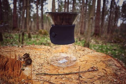 Der gläserne Hario V60 Drip Decanter steht dekorativ auf einem Holzstamm im Wald. Die Kanne an sich ist gläsern, der Silikonkragen sowie der Filterhalter sind schwarz.