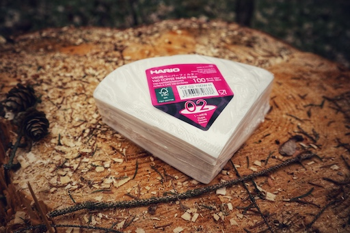 Hario V60 Filterpapier 02 aus EU Produktion. Eine Packung mit 100 Stück liegt dekorativ auf einem Holzstamm im Wald.