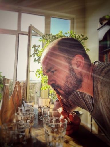 Horst denkt über guten Kaffee für einen Kaffee Kurs nach. er schaut angestrengt auf verschiedene Kaffee Packungen, die auf einem Holztisch stehen. Die Sonne scheint durch das Fenster in den Raum.