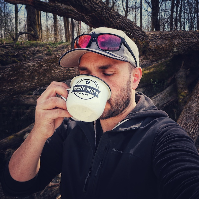 Hier sieht man Horst von einfach mal Kaffee einen Kaffee trinken. Dabei steht er draussen vor einem umgefallenen Baum. Er trägt einen Kapuzenpulli in blau, eine graue Baseball Cap, mit einer verspiegelten Sonnenbrille auf dem Kopf. Die Kaffeetasse ist weiß mit schwarzer Schrift.