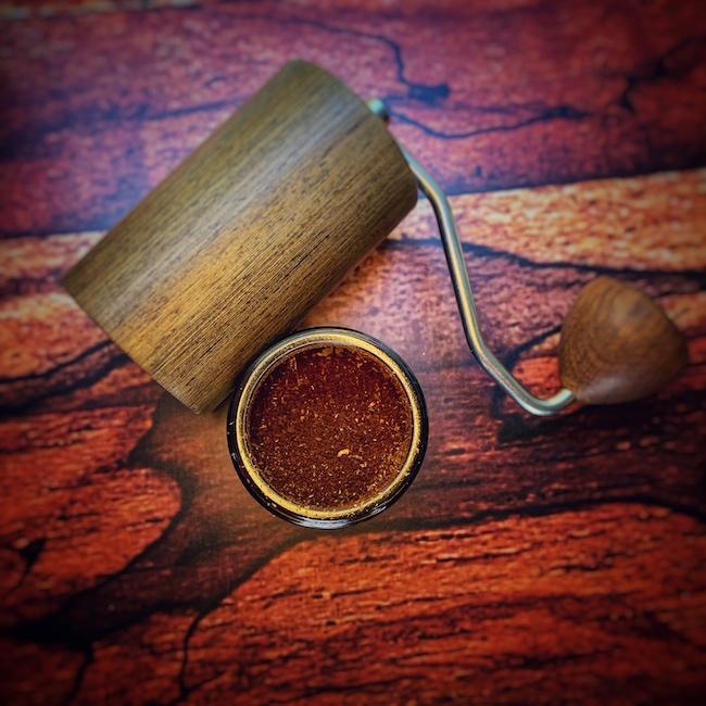 Die Commandante Kaffeemühle aus der Vogelperspektive auf einem Holzbrett. Sie ist auseinandergeschraubt, der Bohnenbehälter liegt und der Mahlgutbehälter steht. In letzterm ist gemahlener Kaffee