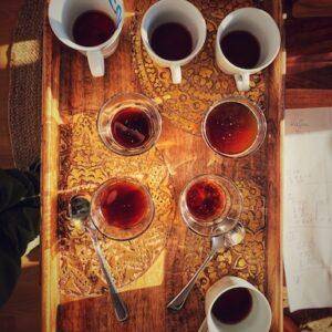 Auf einem braunen Holztablett mit goldenem Muster stehen verschiedene Kaffees und zwei Cupping Löffel. Ein eindeutiges Bild einer sensorischen Reise, die dabei hilft Kaffee ganz neu zu erleben. Wir sehen das Bild aus der Vogelperspektive. Die Sonne scheint in den Raum und die Kaffees wirken Rubin Rot.