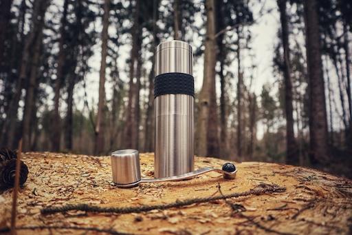 Die Rhinowares Hand Coffee Grinder Kaffeemühle steht dekorativ auf einem Holzstamm im Wald. Sie ist silbern aus Edelstahl gefertigt und hat einen schwarzen Silikonring um den Mahlkörper für besseren Halt. Die Drehkurbel liegt vor ihr und ist ebenfalls aus Metall gefertigt.
