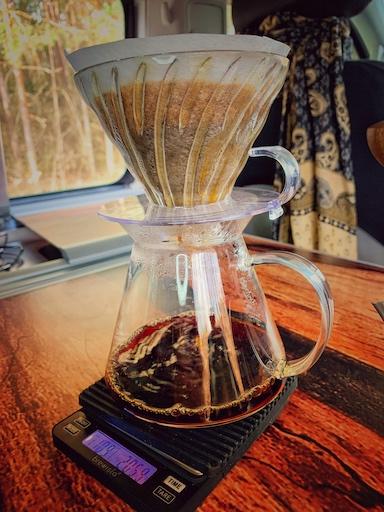 V60 Glas Brewing Kit im Einsatz. Die Gläserne Servierkanne steht auf der Brewista Smart Scale, welche wiederum auf einem Holztisch in einem Camping Fahrzeug steht. Der transparente Glas Filterhalter sitzt auf der Servierkanne und extrahiert hervorragend den gerade brühenden Filterkaffee.
