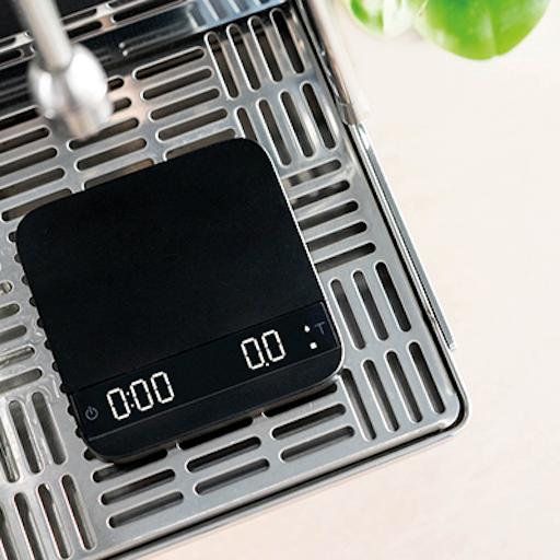 Acaia Lunar Kaffeewaage in schwarz, steht auf einem silbernen Abtropfgitter einer Siebträger Maschine. Sie ist eingeschaltet, aber auf Null Tariert.