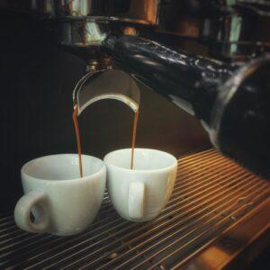 Zwei Espresso Tassen auf dem Abtropfgitter einer schwarzen Siebträgermaschine. Der Kaffee läuft aus den Silbernen Auslässen. Einfach besseren Espresso machen weiht dich in die Geheimnisse dieses Bildes ein. Ein Barista at Home Kurs online und offline möglich.
