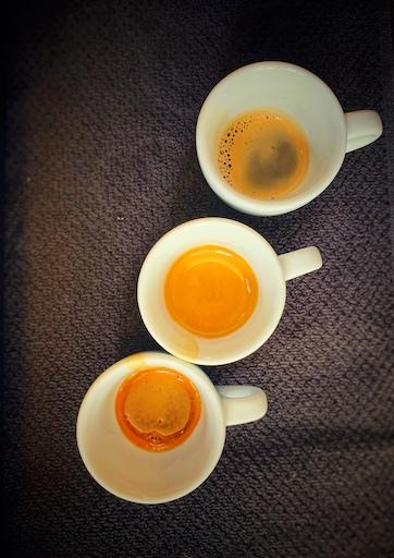 die Phasen des Espresso. Jeweils einen Teil der Espresso Extraktion in einer Tasse aufgefangen. Die weißen Tassen stehen auf einem schwarzen Tuch, wir schauen aus der Vogelperspektive. Dies ist ein Versuch im einfach besseren Espresso machen Barista at Home Kurs.