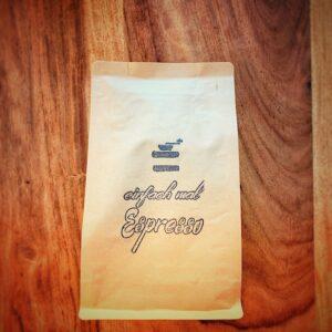 Eine Tüte des einfach mal Espresso Blends liegt auf einem dunklen Holztisch. Wir schauen von oben auf die, auf dem rücken liegende Verpackung. Auf ihrer Vorderseite ist das einfach mal Kaffee Logo gestempelt, mit dem Schriftzug einfach mal Espresso
