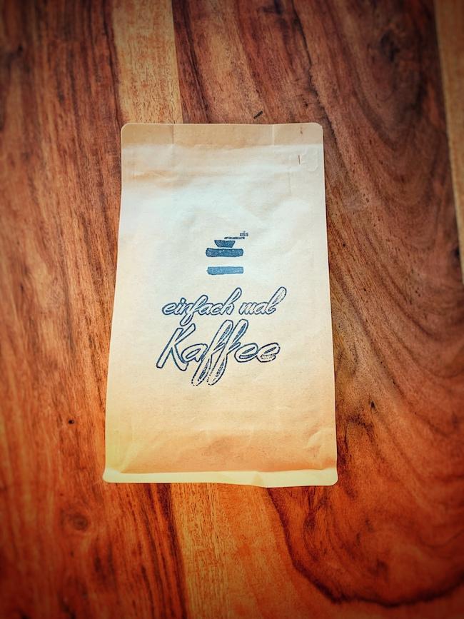 Eine Kaffeetüte aus braunem Papier, bedruckt mit einem einfach mal Kaffee Stempel liegt auf einem dunklen Holztisch. Wir sehen die Szene von oben. Hierbei handelt es sich offensichtlich um einen Filterkaffee Blend.