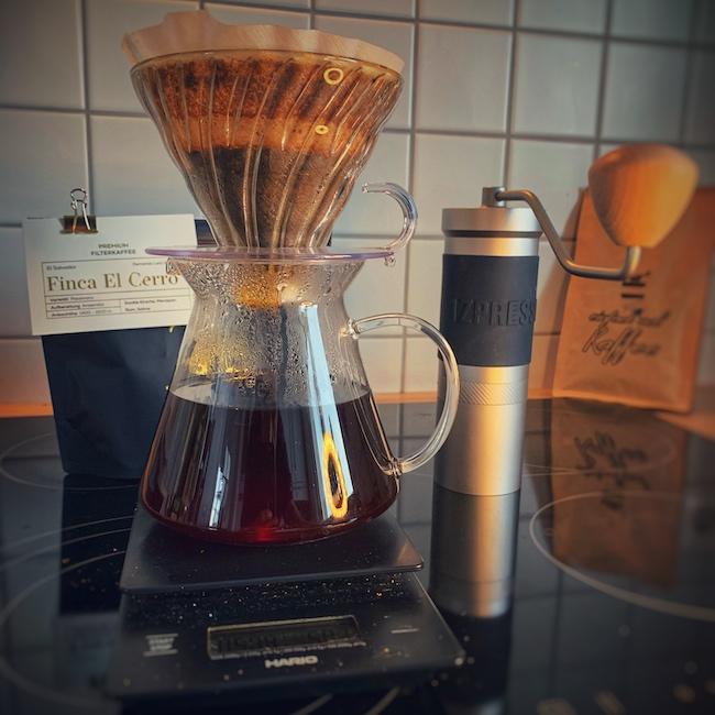 Die perfekte Grundausstattung zum Kaffeekochen. Auf einer schwarzen Untergrund vor einer gefliesten Wand, steht eine JX Pro Kaffee Handmühle, eine Packung guter Kaffee, eine Hario Drip Scale Kaffeewaage und ein gefüllter Hario V60 Glas Brewing Kit.