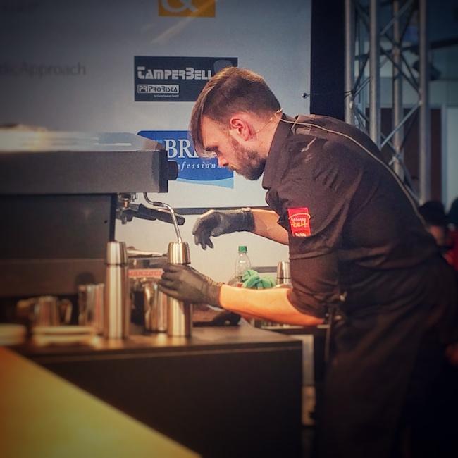 Horst auf der Deutschen Latte Art Meisterschaft 2015. Er trägt ein braunes Hemd, schwarze Handschuhe und eine schwarze Schürze. Gerade ist er dabei eine silberne Thermoskanne aufzuschrauben, während er neben einer La Marzocco Siebträgermaschine steht. Nach diesem Event ist er Head Barista geworden.