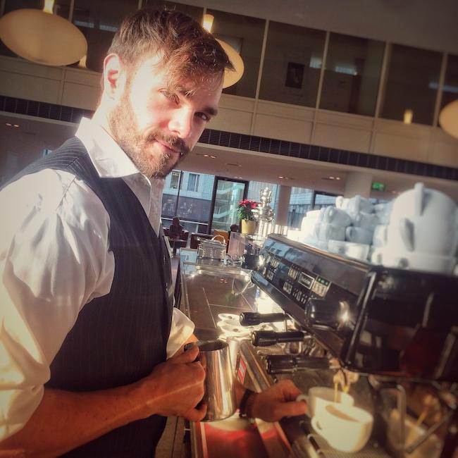 Man sieht Horst von einfach mal Kaffee in seinem Element, als Barista hinter einer Kaffee Bar. Er trägt ein weißes Hemd und eine schwarze Weste, hält ein Milchkännchen aus Edelstahl in der Hand und greift nach zwei weissen Cappuccino Tassen, die auf dem Abtropfgitter der schwarzen Dalla Corte Evo 1 stehen. Im Hintergrund sieht man wohl den Innenbereich einer Cafeteria eines klassischen Bürogebäudes.