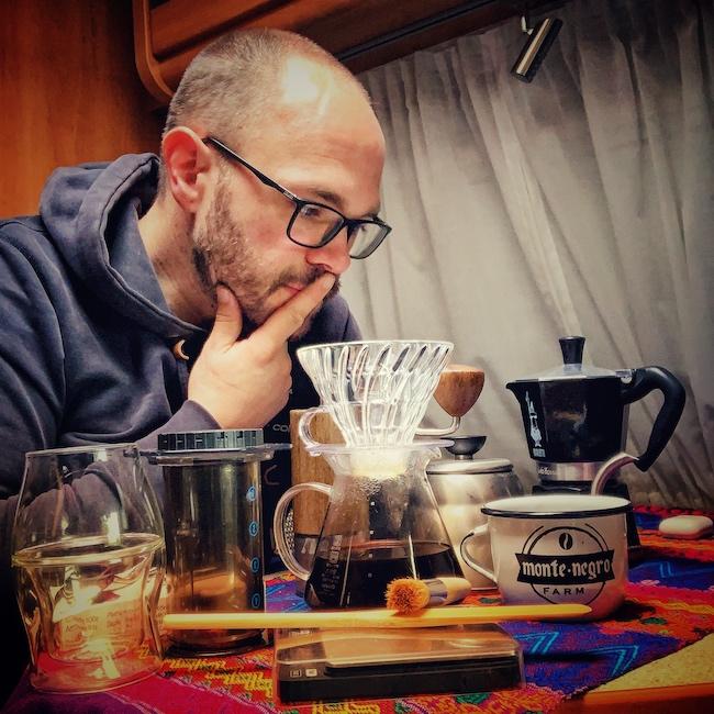 Horst sitzt in seinem Wohnmobil an seinem Tisch und betrachtet seine Grundausstattung zum Kaffee kochen. Er schaut konzentriert. Auf dem Tisch steht alles wichtige: Kaffeemühle, Waage, Hario V60 Kaffeefilter, Mokka Pot, Tasse, Rührstab, Pinsel, Glas und vieles mehr.