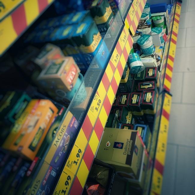 Ein Supermarktregal mit gespickt voll mit Angebotspreisen. Die Schilder sind alle rot gelb leuchtend. Im Regal erkennt man verschiedene Packungen Kaffee, darunter wohl kein Bio Kaffee. Denn für 5,99 das Kilo Lohnt sich Bio Kaffee wohl nicht.