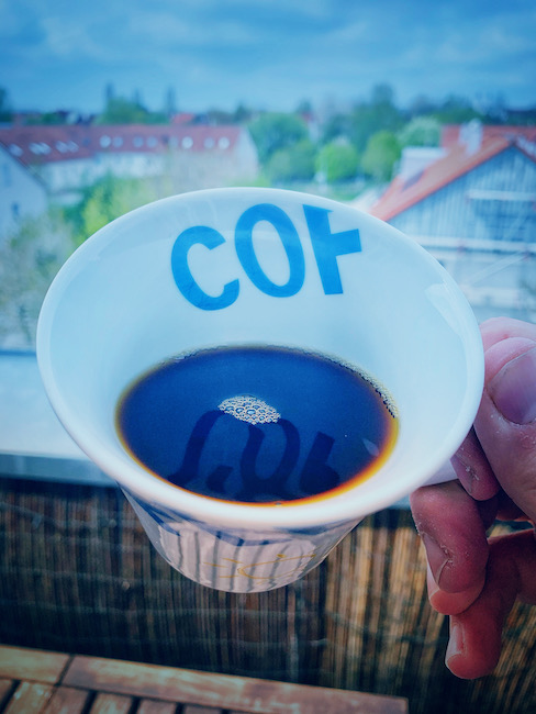 Hier handelt es sich um die gleiche Aufnahme, allerdings mit einer anderen Farbeinstellung. Das Bild wirkt deutlich kälter. Eine weiße Kaffeetasse wird auf einem Balkon hochgehalten, so, dass der Betrachter hineinschauen kann. Das Bild ist aus der Egoperspektive aufgenommen und man erkennt schwarzen Filterkaffee, schätzungsweise ohne Zucker im Kaffee.